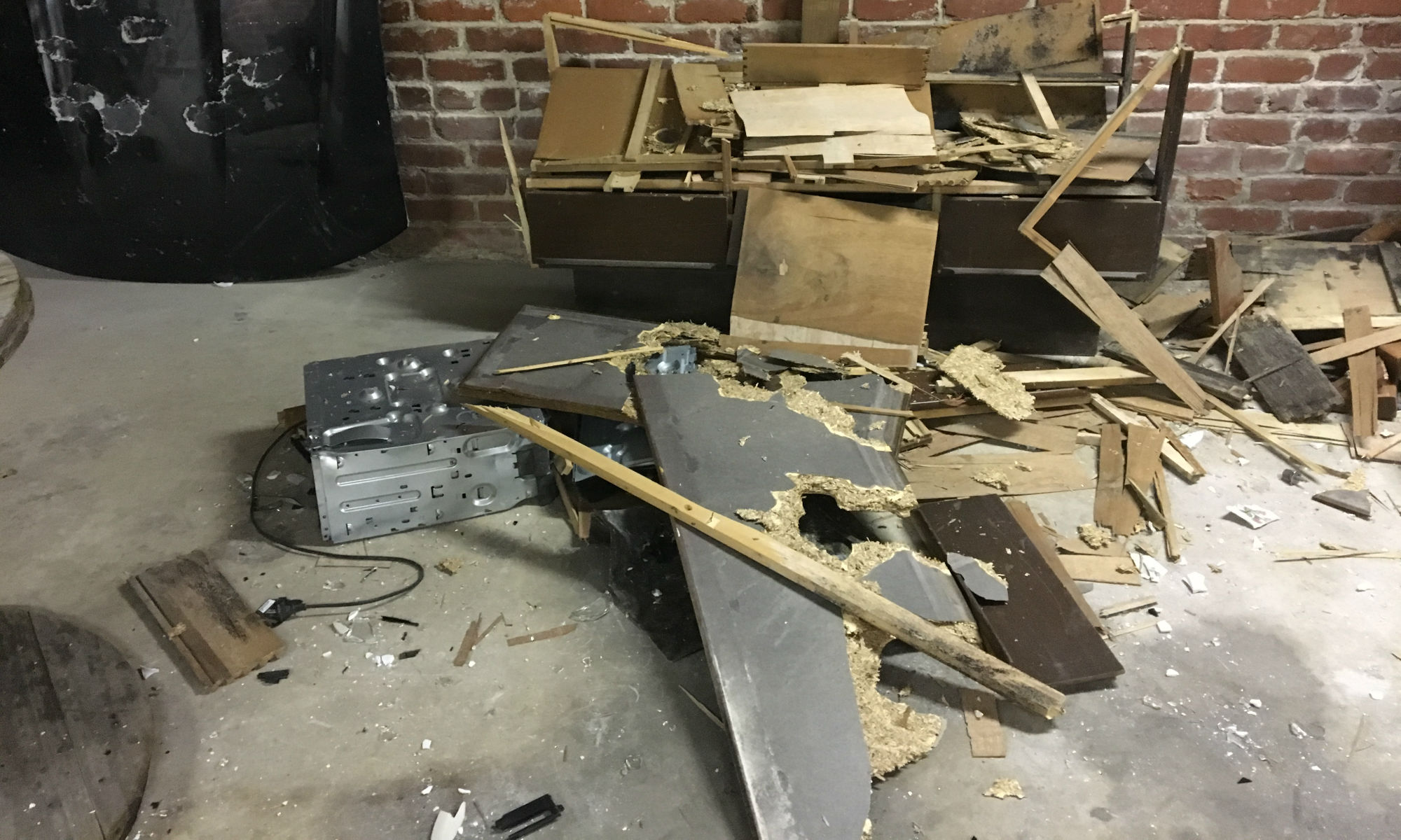 image shows shattered furniture laying in front of car parts and a sledgehammer